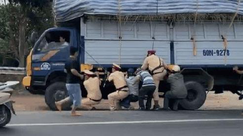 CLIP: CSGT và gần 10 người đàn ông còng lưng cứu xe tải quá khổ