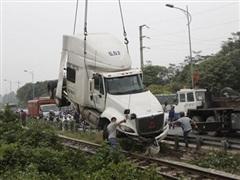 Xe container mất lái, đâm đứt lan can, va chạm mạnh với tàu hỏa