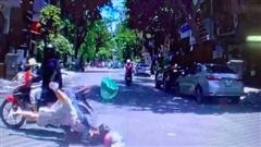 Áo chống nắng cuốn vào bánh xe, cô gái trẻ ngã trước mũi ô tô