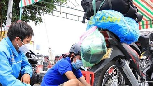 Đội SOS Tháp Mười hỗ trợ sửa xe cho người dân về quê