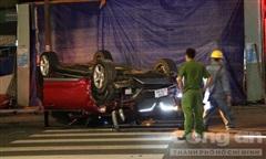 TPHCM: Ôtô húc văng trụ đèn rồi lật ngửa, 2 người bò ra ngoài kêu cứu