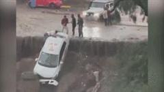 Taxi bị nước lũ cuốn kẹt vào vách đá, nhiều người mạo hiểm giải cứu tài xế