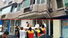 Người dân hợp sức căng rèm hứng cậu bé rơi khỏi cửa sổ chung cư