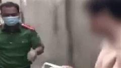 Cởi trần đi đổ rác rồi vô tư ngồi hút thuốc đầu ngõ ngày Hà Nội giãn cách, người đàn ông bị công an đưa về phường