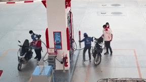 Nữ nhân viên cây xăng la hét vì dẫm phải rắn hổ mang rơi khỏi xe máy